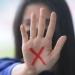 X vermelho na palma da mão sinalizando violência doméstica contra a mulher